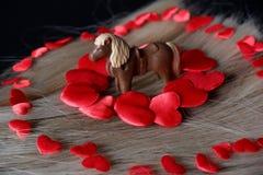 Cavallo circondato dai cuori rossi su crine di cavallo biondo fotografie stock libere da diritti