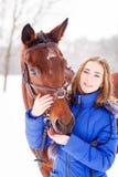 Cavallo di baia d'alimentazione dell'adolescente sul campo di inverno Fotografie Stock Libere da Diritti