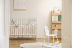 Cavallo a dondolo sulla coperta nell'interno bianco della camera da letto del ` s del bambino con il manifesto del coniglio sopra fotografie stock