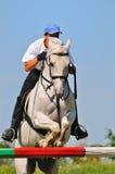 Cavallo e cavaliere grigi sopra un salto Immagine Stock