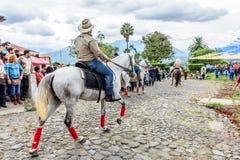 A cavallo giri del cowboy in villaggio, Guatemala Immagini Stock
