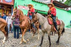 A cavallo giro dei cowboy in villaggio, Guatemala Fotografie Stock