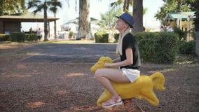 Cavalo bonito novo do brinquedo do passeio da mulher em um campo de jogos do parque filme