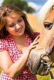 Cavalo das trocas de carícias da mulher na exploração agrícola Imagem de Stock