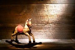 Cavalo de balanço antigo do brinquedo no sótão velho empoeirado da casa Imagem de Stock