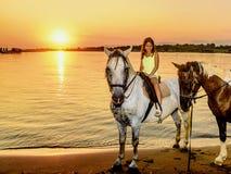 Cavalo de equitação bonito da menina no por do sol pelo mar no Imagem de Stock Royalty Free