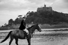 Cavalo de equitação bonito do cavaleiro do cavalo masculino na praia na roupa tradicional da equitação com a montagem do ` s de S Foto de Stock
