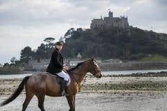 Cavalo de equitação bonito do cavaleiro do cavalo masculino na praia na roupa tradicional da equitação com a montagem do ` s de S Imagem de Stock
