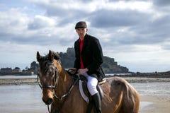 Cavalo de equitação bonito do cavaleiro do cavalo masculino na praia na roupa tradicional da equitação com a montagem do ` s de S Imagem de Stock Royalty Free