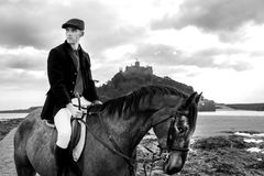 Cavalo de equitação considerável do cavaleiro do cavalo masculino na praia na forma tradicional com a montagem do ` s de St Micha Imagens de Stock