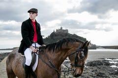 Cavalo de equitação considerável do cavaleiro do cavalo masculino na praia na forma tradicional com a montagem do ` s de St Micha Foto de Stock