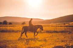 Cavalo de equitação do homem no por do sol imagens de stock