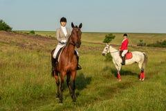 Cavalo de equitação de duas jovens mulheres no parque Caminhada do cavalo no verão fotografia de stock