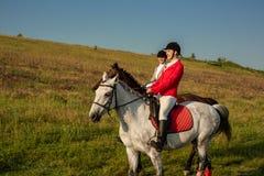 Cavalo de equitação de duas jovens mulheres no parque Caminhada do cavalo no verão foto de stock