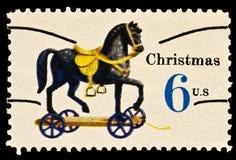 Cavalo do brinquedo no selo do Natal das rodas Imagem de Stock Royalty Free