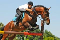 Cavalo e cavaleiro de louro sobre um salto Fotos de Stock Royalty Free