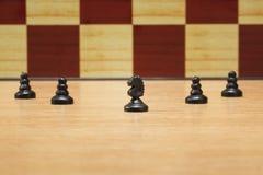 Cavalo e penhores pretos no fundo de uma placa de xadrez Fotos de Stock