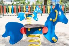 Cavalos de balanço ensolarados no campo de jogos Fotografia de Stock Royalty Free