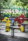 Cavalos de madeira com mola no parque Fotografia de Stock Royalty Free