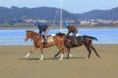 Cavalos que correm ao longo da praia com as montanhas e do mar no fundo São montados por dois cavaleiros foto de stock royalty free