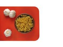Cavatappi макаронных изделий в деревянных шаре и чесноке на оранжевой доске Стоковое Изображение