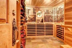 Cave à la maison lumineuse avec les unités de stockage en bois avec des bouteilles Photos libres de droits