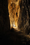 Cave. Dark mystery stone cave with light Stock Photos