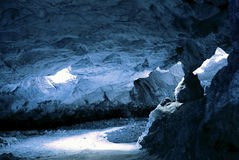 Cave. Blue cave entrance with light passing trough Royalty Free Stock Photo