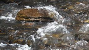 Creek swirling and splashing over a rock stock video footage