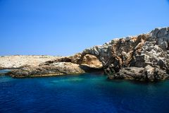 A cave in the deep blue sea of Astypalaia island in Greece royalty free stock image