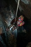Cave descent. Young girl descending on rope in a vertical cave in Apuseni Mountains, Romania. The light comes from below, revealing the depth of the cave. The Royalty Free Stock Image