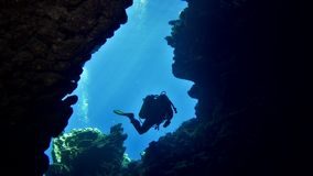 Cave diving underwater scuba divers exploring cave dive. Red Sea Egypt 4K stock video footage