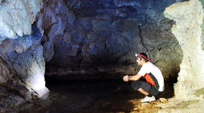 Cave exploring. Young man exploring a cave Stock Photography