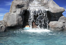 Cave kids. Kids playing in a cave area behind a waterfall in a swimming pool Royalty Free Stock Photos