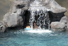 Cave kids. Kids playing in a cave area behind a waterfall in a swimming pool Stock Image