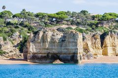 Cave and limestone arch formation. People walking crossing under the arch on the beach. Albufeira area, Algarve Portugal. stock photos