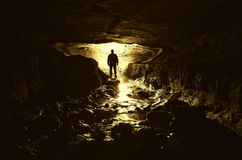 Cave with man silhouette and water