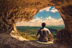 Cave meditation. The man who meditates in a cave overlooking the mountain valley Stock Photography