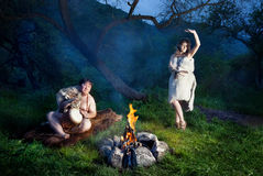 Cave people near bonfire. Caveman dressed in wolf skin playing drum and cave women dancing near bonfire in the forest stock photography