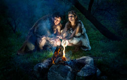 Cave people near bonfire. Cave people dressed in animal roast oneself at bonfire in the forest royalty free stock images