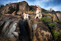 Cave people near drawing rock. Cave people dressed in animal skin near ancient cave drawing in the rocks stock images