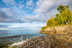 Cave Point Splash. A small wave breaks and splashes under a cloudy blue sky at Door County, Wisconsin's Cave Point on the coast of Lake Michigan Royalty Free Stock Photos