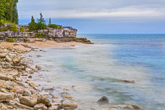 Cave Point Wisconsin Coastline. The rocky coast of Cave Point County Park, in Door County, Wisconsin, is photographed with a long exposure under a cloudy morning stock image