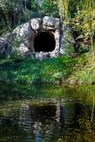 Cave Reflected. A windy day sends ripples through the reflection of a lake side cave Stock Image
