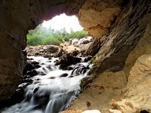 Entrance of a Cave River with a small waterfall into an underground cave. River falling in a small waterfall into an underground limestone cave Royalty Free Stock Images