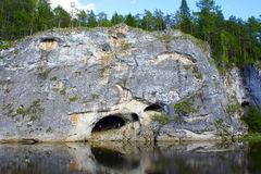 Cave in the rock near river. In summer cave in the rock near the river Stock Image