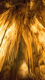 Cave Stalactites. An interior view of a limestone cave showing the rock formations. The image shows the stalactites growing downward to the ground. This image stock images