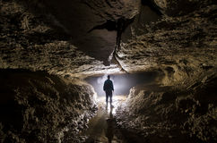 Cave underground with man speleologist and light at entrance Royalty Free Stock Image