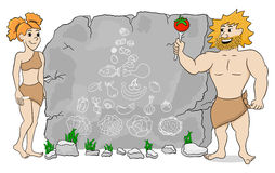 Cave woman explains paleo diet using a food pyramid drawn on sto Stock Images