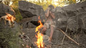 Caveman, ανδρικό αγόρι που κατασκευάζει το πρωτόγονο όπλο πετρών στο στρατόπεδο απόθεμα βίντεο